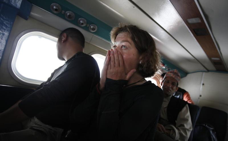 In this Friday, May 24, 2013 photo, a passenger reacts during turbulence as her flight approaches Lukla, Nepal. Carved out of the side of a mountain, the airport was built by Sir Edmund Hillary in 1965, and at an altitude of 2,843 meters (9,325 feet) it has earned the reputation of being one of the most extreme and dangerous airports in the world. (AP Photo/Niranjan Shrestha)