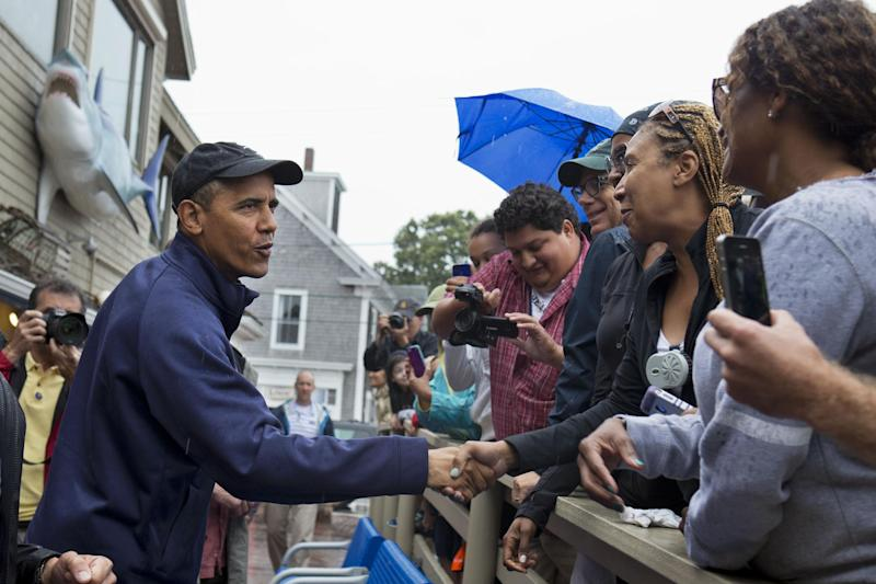 President Barack Obama greets people before ordering lunch at Nancy's restaurant in Oak Bluffs, Mass., on the island of Martha's Vineyard, Tuesday, Aug. 13, 2013. The President and first lady are on vacation on the island. (AP Photo/Jacquelyn Martin)