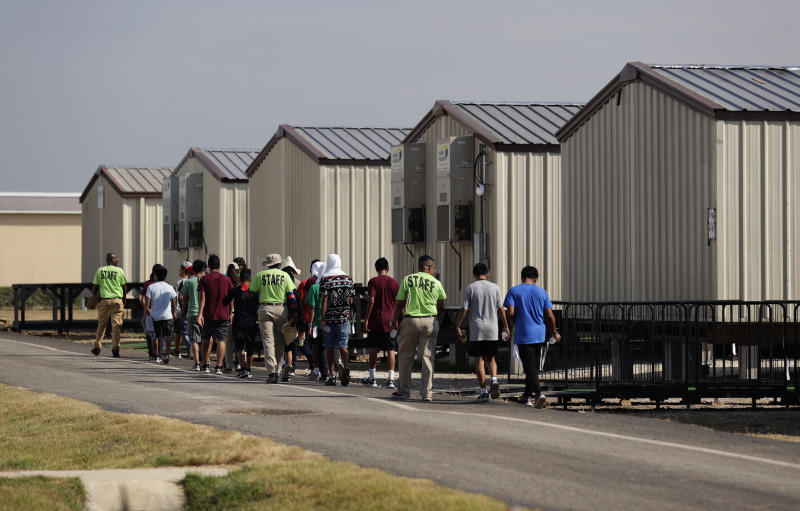 In this July 9, 2019, photo, staff escort immigrants to class at the U.S. government's newest holding center for migrant children in Carrizo Springs, Texas. Following breakfast, children play soccer and then have classes in trailers. (AP Photo/Eric Gay)