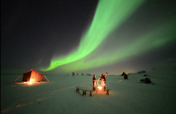 """Northern lights glow over skywatchers high in the Swedish mountains on Feb. 21, 2014 in this image from the video """"Lights Over Lapland"""" by Chad Blakley."""