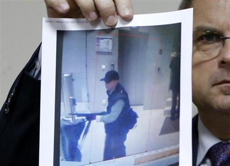 Paris' judiciary police Flaesch shows one of two photographs of the suspect gunman taken from surveillance footage during a news conference in Paris