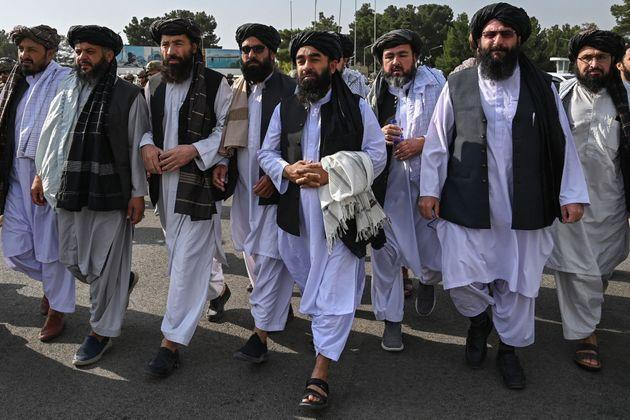 TOPSHOT - Taliban spokesman Zabihullah Mujahid (C, holding shawl) arrives as he is accompanied by officials to address a media conference at the airport in Kabul on August 31, 2021. - The Taliban joyously fired guns into the air and offered words of reconciliation on August 31, as they celebrated defeating the United States and returning to power after two decades of war that devastated Afghanistan. (Photo by WAKIL KOHSAR / AFP) (Photo by WAKIL KOHSAR/AFP via Getty Images) (Photo: WAKIL KOHSAR via Getty Images)