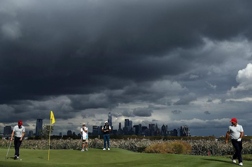 Patrick Reed (R) and Jordan Spieth of the US Team walk on the 10th green as Jason Day of the International team (C) looks on during Saturday four-ball matches of the Presidents Cup, at Liberty National Golf Club in Jersey City, on September 30, 2017 (AFP Photo/Patrick Smith)