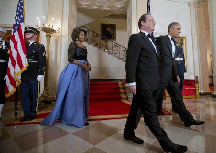 First Lady Michelle Obama, left, follows her husband President Barack Obama and French President Francois Hollande, center, after posing at the Grand Staircase, Tuesday, Feb. 11, 2014, for a State Dinner at the White House in Washington. (AP Photo/Pablo Martinez Monsivais)