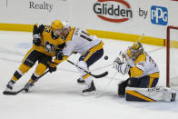 Nashville Predators goaltender Pekka Rinne stops a shot by Pittsburgh Penguins' Teddy Blueger (53) as Mattias Ekholm (14) defends during the first period of an NHL hockey game, Saturday, Dec. 28, 2019, in Pittsburgh. (AP Photo/Keith Srakocic)