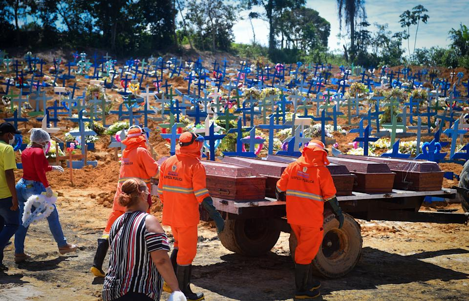 29 April 2020, Brazil, Manaus: Cemetery workers, followed by relatives of the dead wearing face masks against the spread of Covid-19, drive coffins to a mass grave. In view of the increasing number of corona infections, the health service in Manaus is at its limit. A refrigerated container for storing corpses was set up in front of a hospital, mass graves were dug. The number of Covid-19 related deaths in the country rose to 5017 - surpassing China, which officially registered 4643 deaths. The ultra-right-wing President Bolsonaro plays down the virus. Photo: Chico Batata/dpa (Photo by Chico Batata/picture alliance via Getty Images)