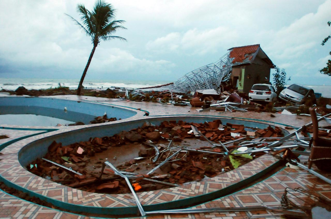 <p>Here, a hotel pool has been filled with debris and vehicles swept along by powerful waves. </p>