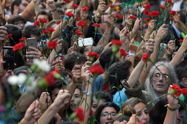 <p>People hold flowers during a protest near the Economy headquarters of Catalonia's regional government in Barcelona on Sept. 20, 2017. (Photo: Lluis Gene/AFP/Getty Images) </p>