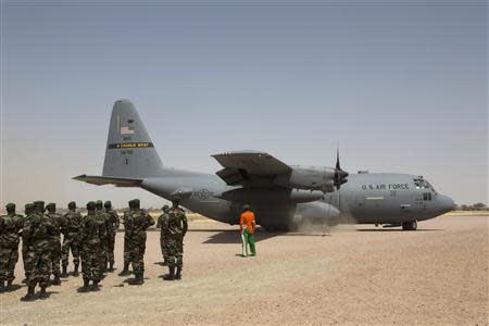 A C-130 U.S. Air Force plane lands as Nigerien soldiers stand in formation during the Flintlock military exercise in Diffa, March 8, 2014. REUTERS/Joe Penney