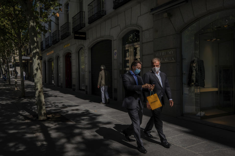 Two men walk in the upmarket neighborhood of Salamanca in Madrid, Spain, Monday, Sept. 28, 2020. The extended region around Madrid, comprising a population of 6.6 million, is struggling to control coronavirus outbreaks. Heightened restrictions in some of Madrid's working-class neighborhoods brought a heated debate over the prevalence of inequality in Spain. (AP Photo/Bernat Armangue)