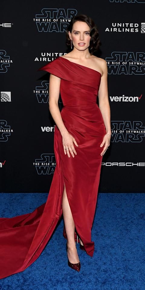 "<p>Daisy Ridley stunned at the <em>Star Wars: The Rise of Skywalker</em> premiere in a scarlet <a href=""https://click.linksynergy.com/deeplink?id=93xLBvPhAeE&mid=37385&murl=https%3A%2F%2Fwww.modaoperandi.com%2Foscar-de-la-renta%2Fwomen&u1=IS%2CDaisyRidley%2Canesta%2C%2CIMA%2C3507596%2C201912%2CI"" target=""_blank"">Oscar de la Renta</a> gown with droop earrings and coordinating pumps.</p>"