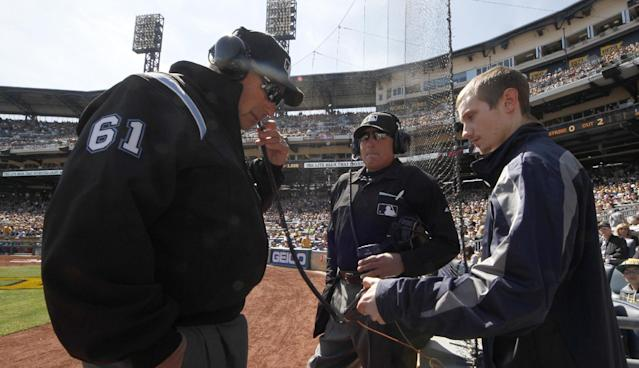 First base umpire Bob Davidson (61) and home plate umpire John Hirschbeck, center, talk over headsets as a play at first base is being reviewed in the fifth inning during the opening day baseball game between the Pittsburgh Pirates and the Chicago Cubs on Monday, March 31, 2014, in Pittsburgh. Chicago Cubs manager Rick Renteria requested a replay on an out call. (AP Photo/Gene Puskar)