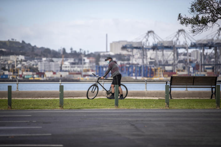 A cyclist wearing a mask pauses along the waterfront in Auckland, New Zealand, on Thursday, Aug. 19, 2021. Japan, Australia and New Zealand all got through the first year of the coronavirus pandemic in relatively good shape, but now are taking diverging paths in dealing with new outbreaks of the fast-spreading delta variant. (Michael Craig/New Zealand Herald via AP)
