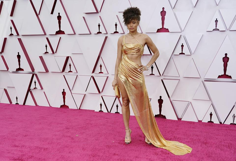 """<p>Wearing a gold <a href=""""https://www.popsugar.com/fashion/andra-day-vera-wang-dress-oscars-2021-48288720"""" class=""""link rapid-noclick-resp"""" rel=""""nofollow noopener"""" target=""""_blank"""" data-ylk=""""slk:Vera Wang gown"""">Vera Wang gown</a> with cutouts and a slit and Tiffany &amp; Co. jewels.</p>"""