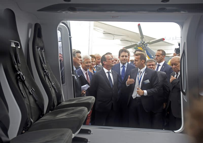 French President Francois Hollande listens to the explanations of Chief Executive Officer of Airbus Helicopters Guillaume Faury during the inauguration of the 51st Paris Air Show at Le Bourget airport near Paris