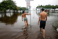 <p>Christian Phillips, 19, (L), and Ilya Hanzli, 17, walk through flooding caused by Hurricane Lane in Hilo, Hawaii, Aug. 25, 2018. (Photo: Terray Sylvester/Reuters) </p>