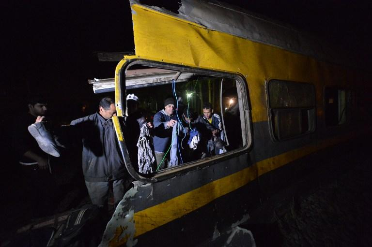 People inspect at the wreckage of a train in the Giza in Badrashin, about 40 km west of Cairo, on January 15, 2013, at least 19people where killed  and injured 105.  The train carrying conscripts from south Egypt to Cairo derailed in the Giza neighbourhood of Badrasheen, state media reported.  Giza governor Ali Abdelrahman said emergency services were at the scene and ambulances were ferrying the injured to hospital.  The accident is the latest in a string of transport disasters plaguing the country.    AFP PHOTO / KHALED DESOUKI