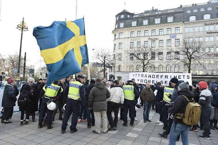 """Stockholm police talk to participants of a movement called """"The People's Demonstration"""" which held a protest at Norrmalmstorg square on January 30, 2016 (AFP Photo/Marcus Ericsson/TT)"""