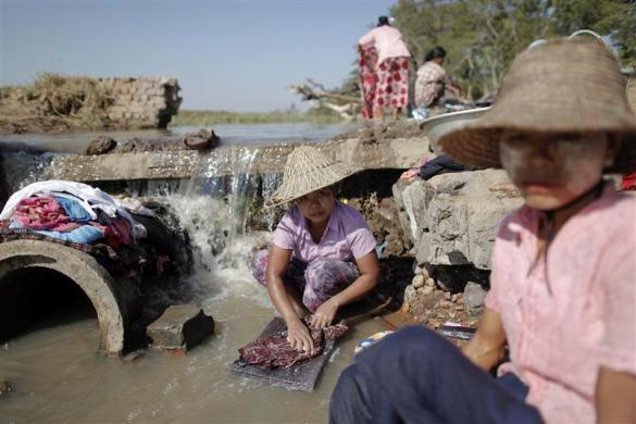 Women wash clothes at a river in the outskirts of capital Naypyitaw, January 24, 2012.
