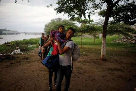 A central American migrant holds his daughter after crossing the Suchiate river on a raft from Tecun Uman, in Guatemala, to Ciudad Hidalgo, as seen from Ciudad Hidalgo