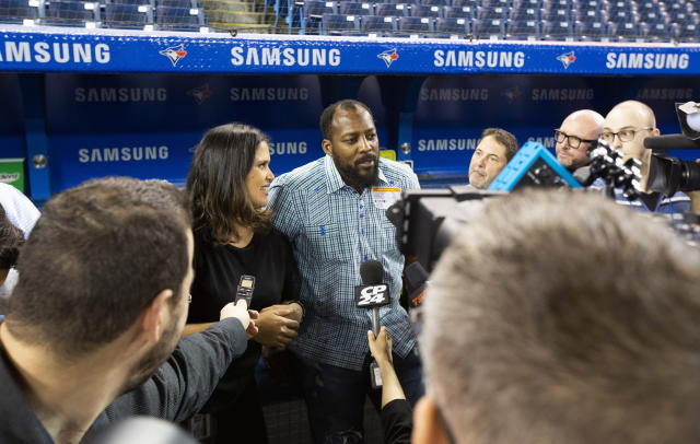 Former baseball player Vladimir Guerrero, center, talks to the media about his son, Toronto Blue Jays rookie Vladimir Guerrero Jr., ahead of his son's major league debut against the Oakland Athletics in a baseball game in Toronto, Friday April 26, 2019. (Mark Blinch/The Canadian Press via AP)