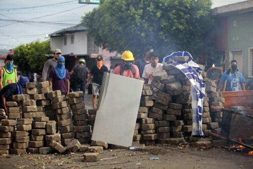 Demonstrators protect themselves behind barricades last month in the Nicaraguan town of Masaya