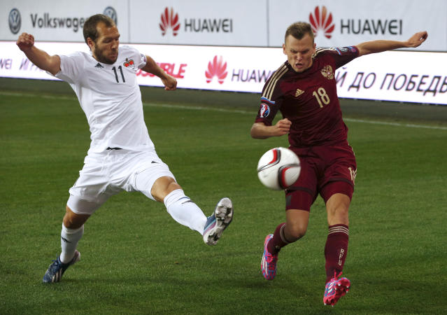 FILE - In this Monday, Sept. 8, 2014 file photo, Liechtenstein's Franz Burgmeier, left, blocks the shot by Russia's Denis Cheryshev during their Euro 2016 qualifying soccer match at Arena Khimki stadium in Moscow, Russia. Russian players don't tend to play their club football abroad, but there's one big exception in midfield - Denis Cheryshev. The winger came through the Real Madrid youth system when his father was coaching there and is now at Villarreal, but frequent injuries have dented hopes he can add some spice to the national team. (AP Photo/Pavel Golovkin, file)