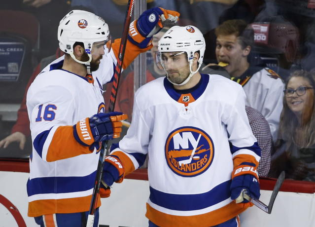 New York Islanders' Jordan Eberle, right, celebrates his goal with teammate Andrew Ladd during first period NHL hockey action against the Calgary Flames in Calgary, Sunday, March 11, 2018. (Jeff McIntosh/The Canadian Press via AP)
