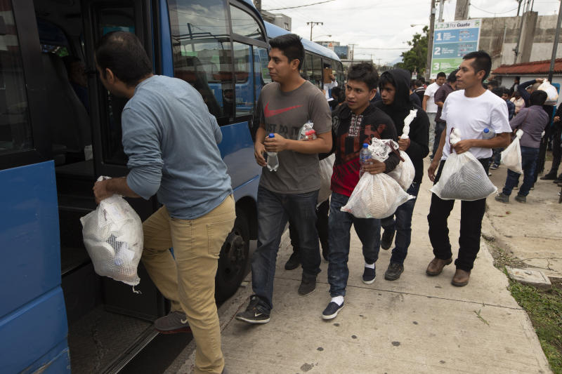 Guatemalan men who were deported from the United States, board a bus after arriving at the Air Force Base in Guatemala City, Tuesday, July 16, 2019. Nearly 200 Guatemalan migrants have been deported on Tuesday, the day the Trump administration planned to launch a drastic policy change designed to end asylum protections for most migrants who travel through another country to reach the United States. (AP Photo/Moises Castillo)