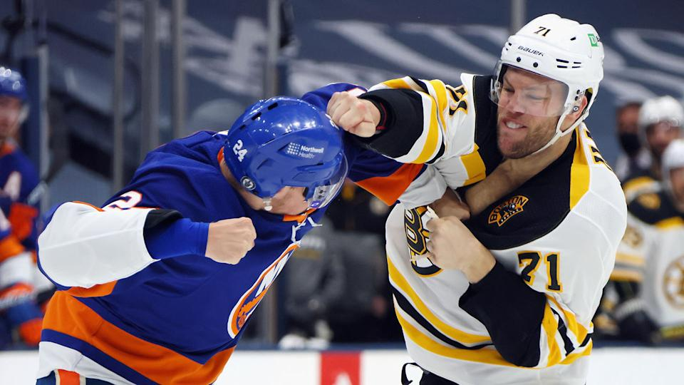 UNIONDALE, NEW YORK - JUNE 05: Taylor Hall #71 of the Boston Bruins and Scott Mayfield #24 of the New York Islanders fight during the first period in Game Four of the Second Round of the 2021 NHL Stanley Cup Playoffs at the Nassau Coliseum on June 05, 2021 in Uniondale, New York. (Photo by Bruce Bennett/Getty Images)