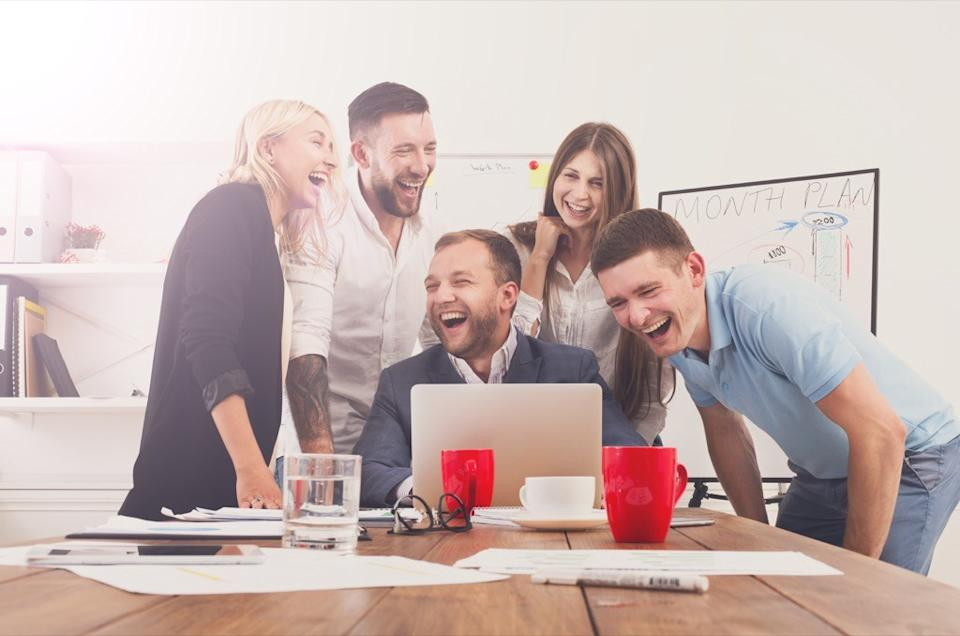 coworkers gathered around a laptop laughing - wholesome memes