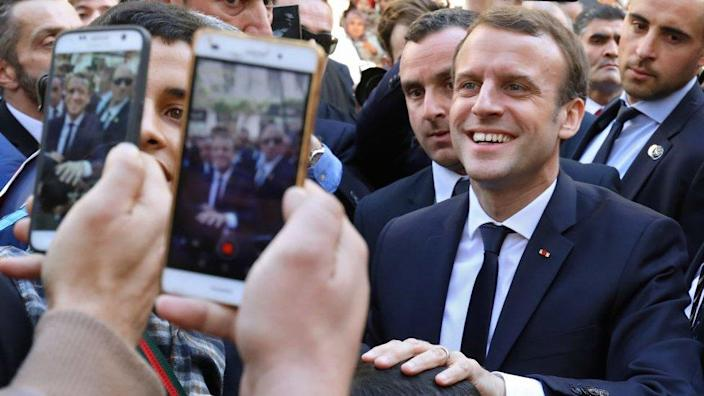 French President Emmanuel Macron is surrounded by security as he greets children in the streets of Algiers on December 6, 2017.