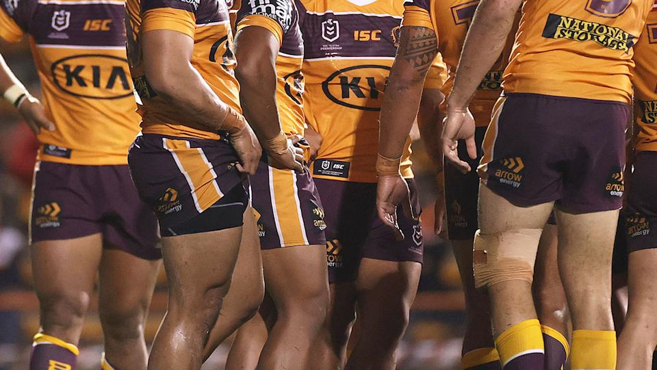 Pictured here, Brisbane Broncos players in a huddle during a match.