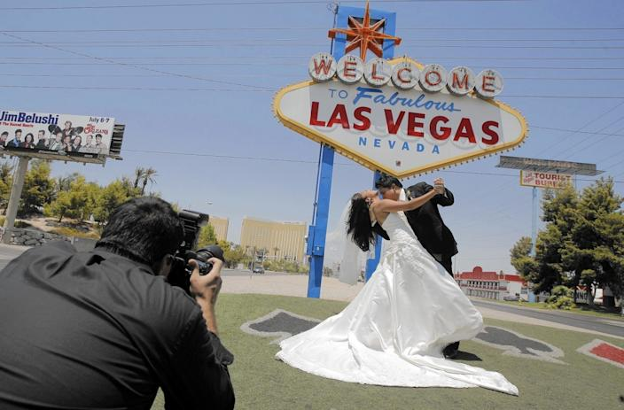 "A couple get married with the ""Welcome to Fabulous Las Vegas"" sign in the background."