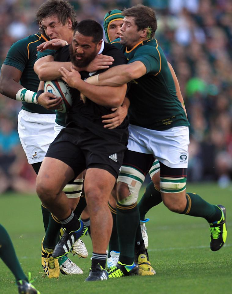New Zealand's Charlie Faumuina, center, is tackled by South Africa's Willem Alberts, right, and teammates during their Rugby Championship match at Ellis Park Stadium in Johannesburg, South Africa, Saturday, Oct. 5, 2013. (AP Photo/Themba Hadebe)
