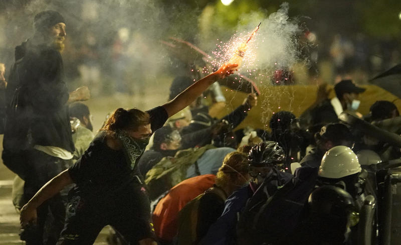 A protester launches a projectile toward police during clashes outside the Kenosha County Courthouse in Wisconsin. Source: AP