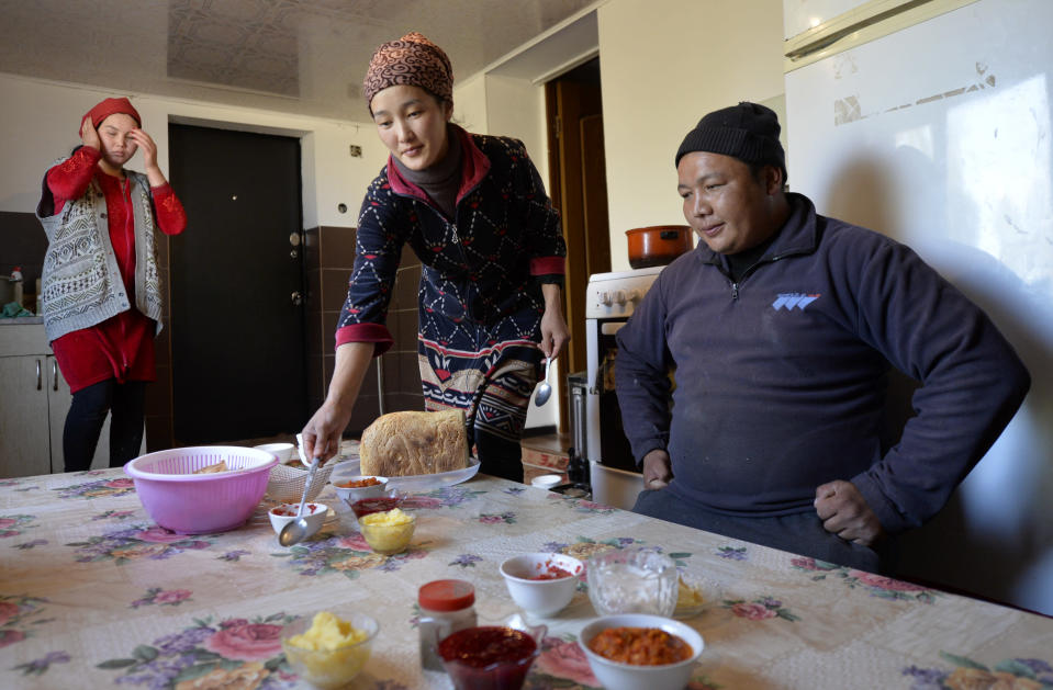 Adilet Kaliyev sits while his wife Burul, center, serves a lunch for him before his heading to the mountains to drive a flock of sheeps at their family house in Tash Bashat village, about 24 kilometers (15 miles) southeast of Bishkek, Kyrgyzstan, Saturday, Oct. 17, 2020. Zarina, wife of his brother Azret Kaliyev in on the left. Kyrgyzstan, one of the poorest countries to emerge from the former Soviet Union, saw its president forced out by protesters earlier this month, but the political turmoil hasn't touched that village nestled in the scenic Ala-Too mountains where life follows centuries-old rites. (AP Photo/Vladimir Voronin)