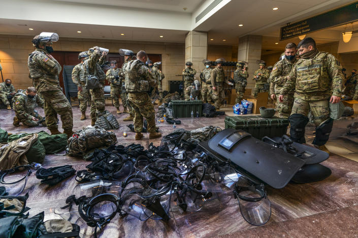 Members of the National Guard gather inside the Capitol Visitor Center, Wednesday, Jan. 13, 2021, in Washington as the House of Representatives continues with its fast-moving House vote to impeach President Donald Trump, a week after a mob of Trump supporters stormed the U.S. Capitol. (AP Photo/Manuel Balce Ceneta)