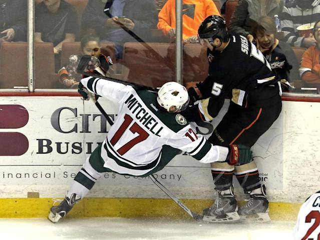 Anaheim Ducks defenseman Luca Sbisa (5), of Italy, and Minnesota Wild center Torrey Mitchell (17) tangle in the first period of an NHL hockey game in Anaheim, Calif., Tuesday, Jan. 28, 2014. (AP Photo/Reed Saxon)