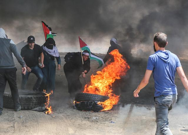 <p>Palestinians set tires on fire in response to Israel's intervention during a protest, organized to mark the 70th anniversary of Nakba, also known as Day of the Catastrophe in 1948, and against the relocation of the U.S. Embassy from Tel Aviv to Jerusalem, near the Gaza-Israel border in Khan Younis on May 14, 2018. (Photo: Mustafa Hassona/Anadolu Agency/Getty Images) </p>