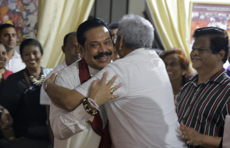 Newly appointed Sri Lankan Prime Minister Mahinda Rajapaksa, left, embraces his brother former defense secretary Gotabhaya Rajapaksa at a Buddhist temple in Colombo, Sri Lanka, Friday, Oct. 26, 2018. Sri Lankan President Maithripala Sirisena sacked the country's prime minister and his Cabinet and replaced him with a former strongman, creating what some observers said could be a constitutional crisis in the South Asian island nation. (AP Photo/Eranga Jayawardena)