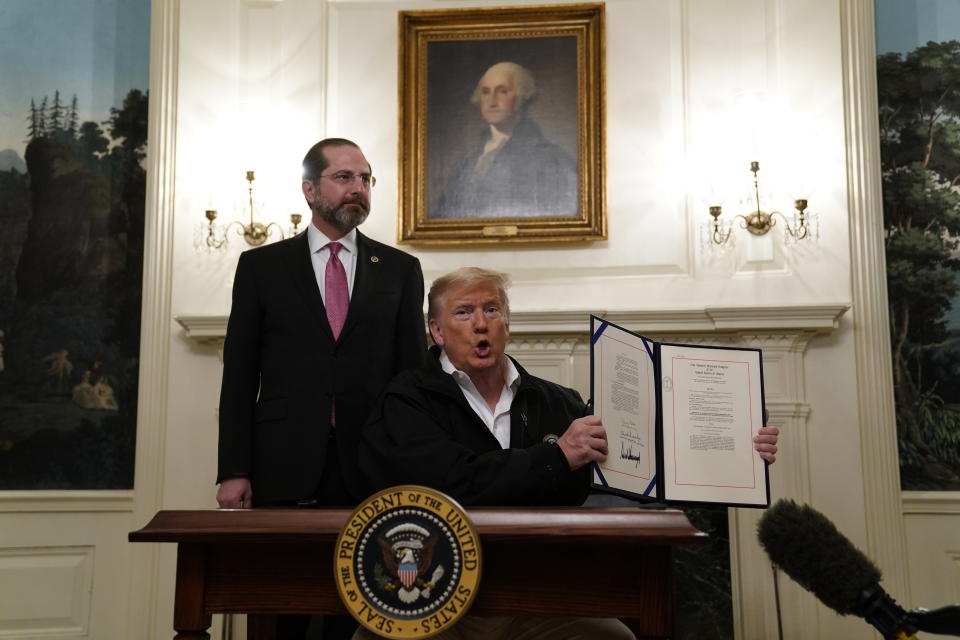 President Donald Trump holds up an $8.3 billion bill to fight the coronavirus outbreak in the U.S., Friday, March 6, 2020 at the White House in Washington after signing, as Department of Health and Human Services Secretary Alex Azar, looks on. The legislation provides federal public health agencies with money for vaccines, tests and potential treatments and helps state and local governments prepare and respond to the threat. The rapid spread of the virus has rocked financial markets, interrupted travel and threatens to affect everyday life in the United States. (AP Photo/Evan Vucci)