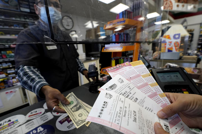 A customer purchases Powerball and Mega Millions tickets at a convenience store in Northbrook, Ill., Wednesday, Jan. 6, 2021. (AP Photo/Nam Y. Huh)