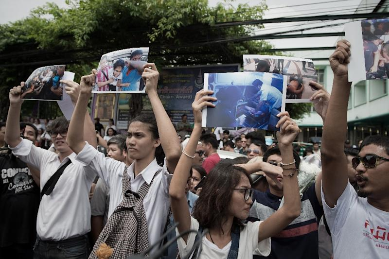 Supporters of anti-coup activists gather outside a police station in Bangkok on June 24, 2015, cheering them on and holding up photos of the protesters who were pulled away by police last month (AFP Photo/Nicolas Asfouri)