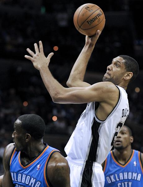 San Antonio Spurs' Tim Duncan, right, shoots over Oklahoma City Thunder's Kendrick Perkins during the first half of an NBA basketball game, Monday, March 11, 2013, in San Antonio. (AP Photo/Darren Abate)