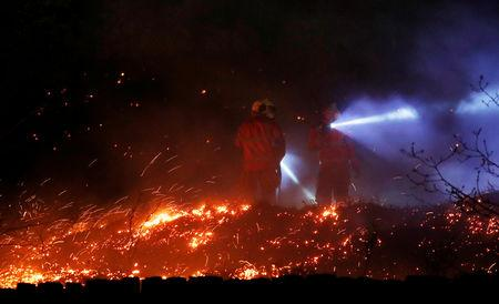 Firefighters tackle a fire on a patch of moorland above the village of Uppermill, Britain, April 22, 2019. REUTERS/Phil Noble