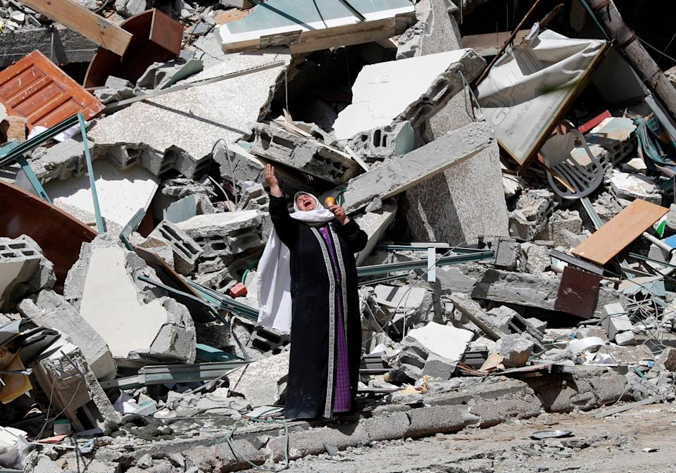 May 16, 2021:  A woman reacts while standing near the rubble of a building that was destroyed by an Israeli airstrike on Saturday that housed The Associated Press, broadcaster Al-Jazeera and other media outlets, in Gaza City.