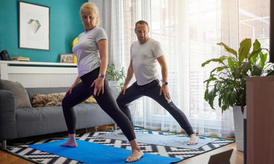 Couple practising yoga at home