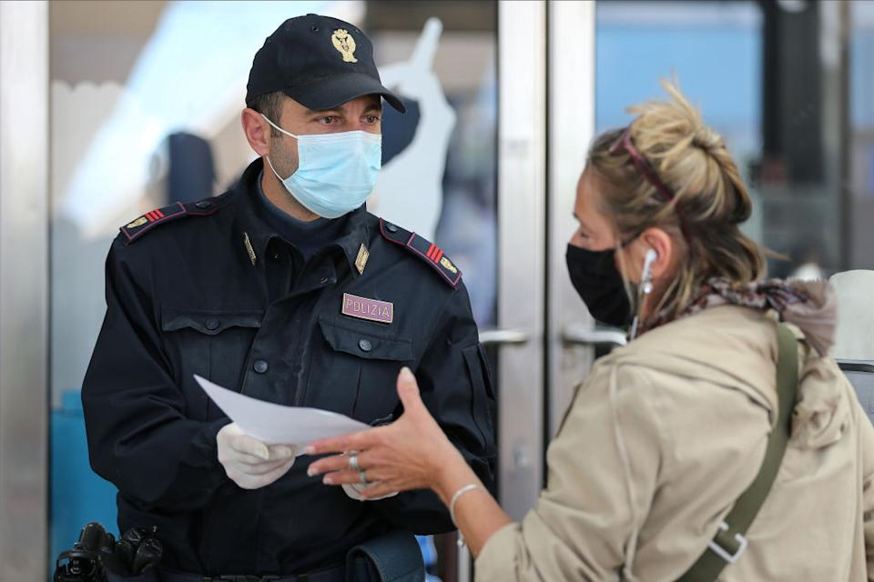 A woman delivers a self-declaration to a policeman in the Naples railway station.