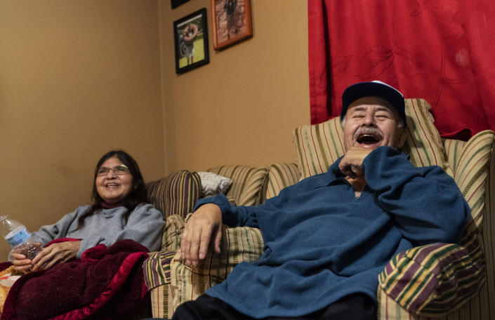 """Mario Valdez, 62, right, laughs while watching television with his wife, Reyna, 52, at their home in Central Falls, R.I., Thursday, Feb. 18, 2021. """"I feel happy,"""" said Valdez, a school bus driver shortly after receiving his second and final dose. """"Too many people here have COVID. It's better to be safe."""" (AP Photo/David Goldman)"""